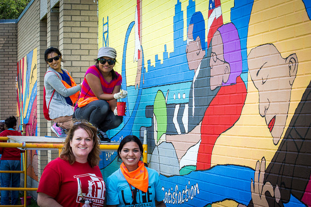 a group of volunteers painting a mural in the Cody Rouge neighborhood